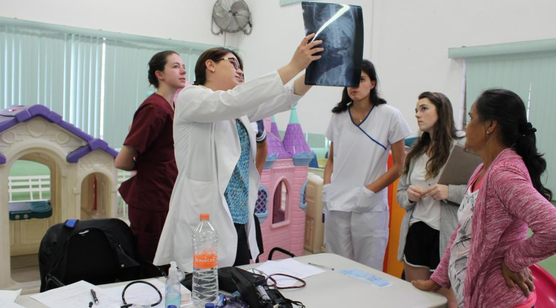 Medical interns on their Medicine internships in Mexico examine an X-Ray with a local doctor explaining what they see.
